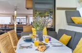 Guest dining table with white table cloth, grey cushions and yellow pillow