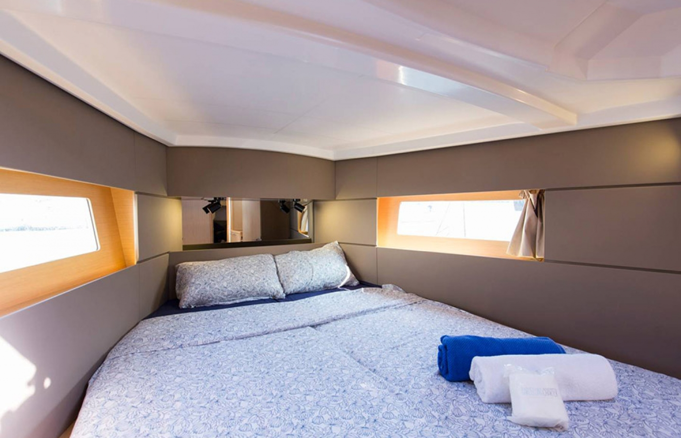 Large double bed inside the cabin including two windows and storage