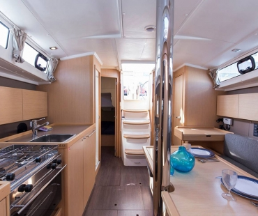 Silver kitchen appliances along with seating area and staircase leading to the top deck